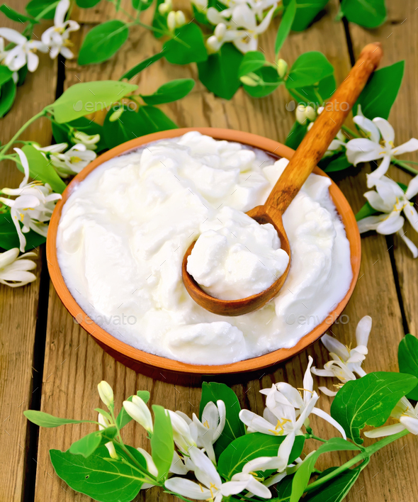 Yogurt in clay bowl with spoon and flowers of honeysuckle - Stock Photo - Images