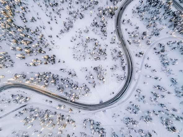 Aerial view of Curvy Windy Road in snow covered forest in Winter Finland - Stock Photo - Images