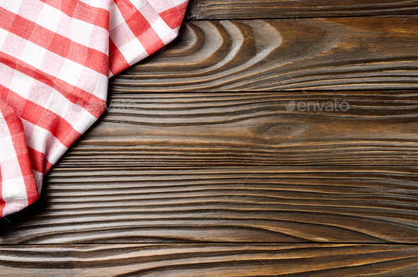 Red checkered napkin on brown wooden kitchen table with copy-space. Top view - Stock Photo - Images