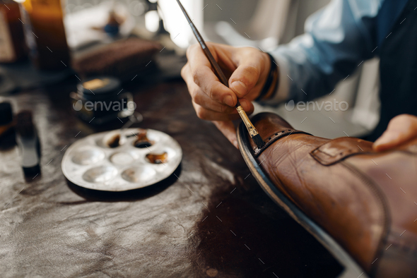 Shoemaker with brush tints shoes, footwear repair - Stock Photo - Images