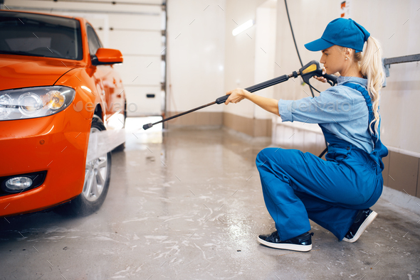 Female washer cleans wheel with high pressure gun - Stock Photo - Images