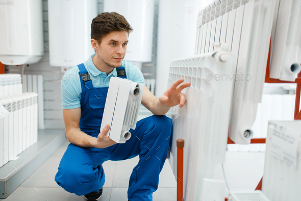 Plumber shows heating radiator section, plumbering - Stock Photo - Images