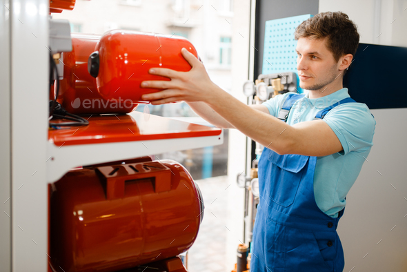 Plumber choosing expansion tank for water pump - Stock Photo - Images