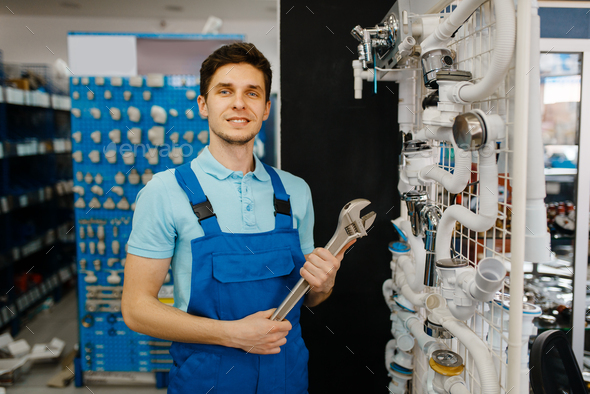 Plumber with pipe wrenches poses at the showcase - Stock Photo - Images