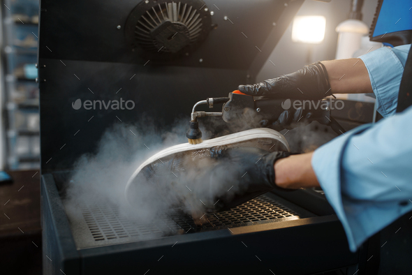 Shoemaker processes the shoes on special machine - Stock Photo - Images