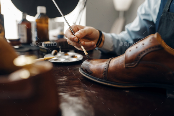 Bootmaker with brush tints shoes, footwear repair - Stock Photo - Images