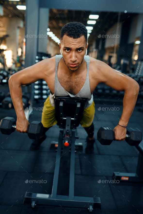 Man doing exercise with dumbbells on the bench - Stock Photo - Images