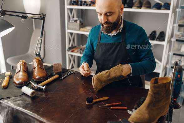 Shoemaker stitches the shoe, footwear repair - Stock Photo - Images