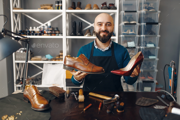 Bootmaker shows repaired shoes, footwear repair - Stock Photo - Images