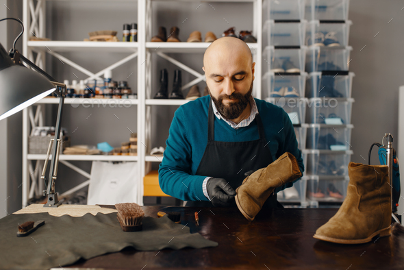 Shoemaker sharpens the shoe sole, footwear repair - Stock Photo - Images