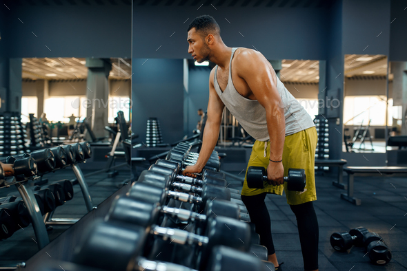 Muscular man choosing heavy dumbbells in gym - Stock Photo - Images