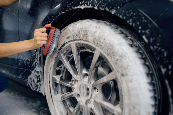 Female washer with brush cleans wheel, car wash - Stock Photo - Images