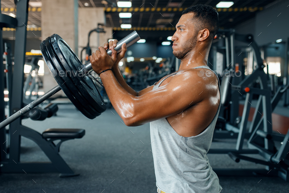 Sporsman doing exercise with barbell in gym - Stock Photo - Images