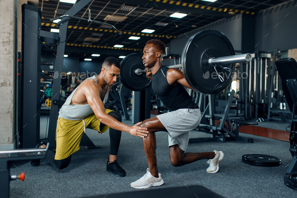 Muscular sportsman and trainer on training in gym - Stock Photo - Images