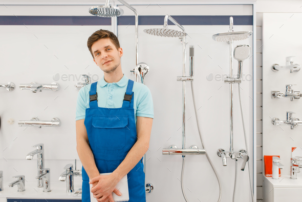 Plumber at showcase with boilers, plumbering store - Stock Photo - Images