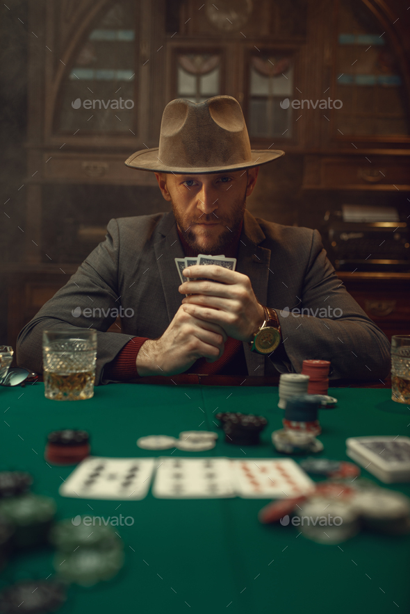 Poker player in suit and hat plays in casino - Stock Photo - Images
