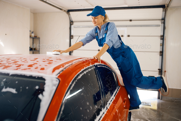 Female washer wipes the automobile windshield - Stock Photo - Images