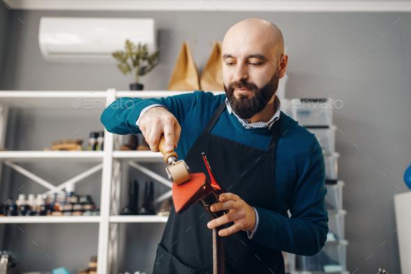 Shoemaker repairing shoe, footwear repair service - Stock Photo - Images
