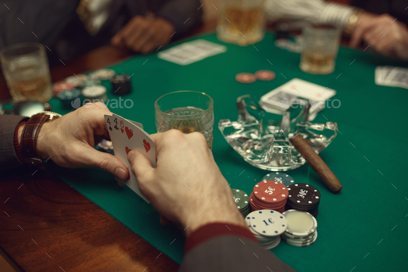 Poker players at the table with cards and chips - Stock Photo - Images
