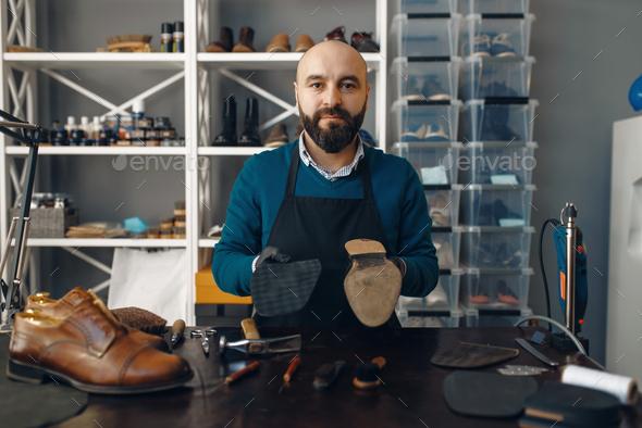 Bootmaker repairing the shoe, footwear repair - Stock Photo - Images