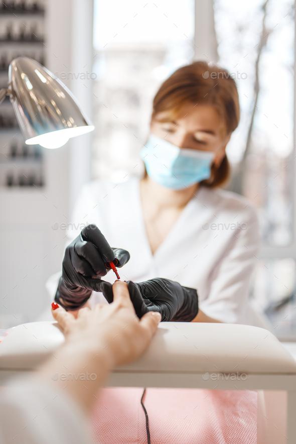 Cosmetology salon, manicure, varnish application - Stock Photo - Images