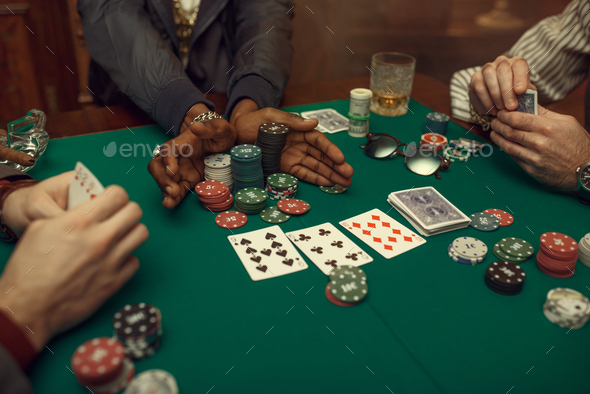 Poker players hands, gaming table on background - Stock Photo - Images