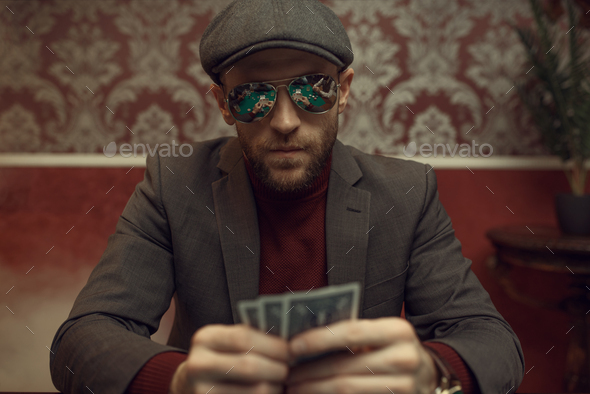Serious poker player playing in casino - Stock Photo - Images