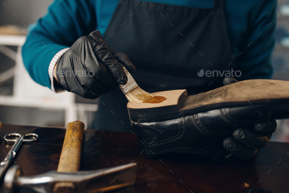 Shoemaker smears glue to the shoe, footwear repair - Stock Photo - Images