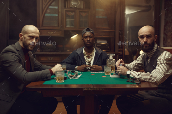 Poker players with cards playing in casino - Stock Photo - Images