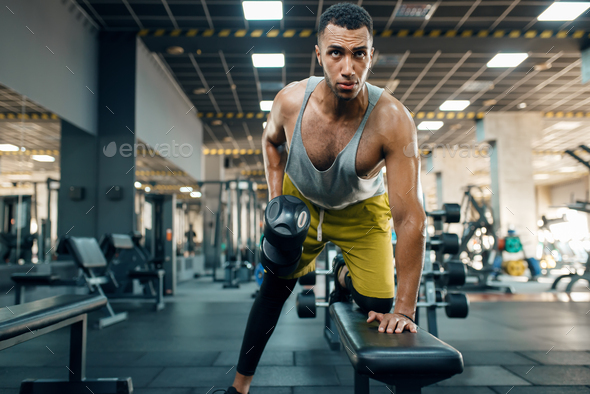 Athlete doing exercise with dumbbells on the bench - Stock Photo - Images