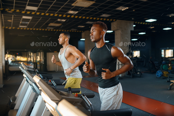 Two athletes runs on treadmill, training in gym - Stock Photo - Images