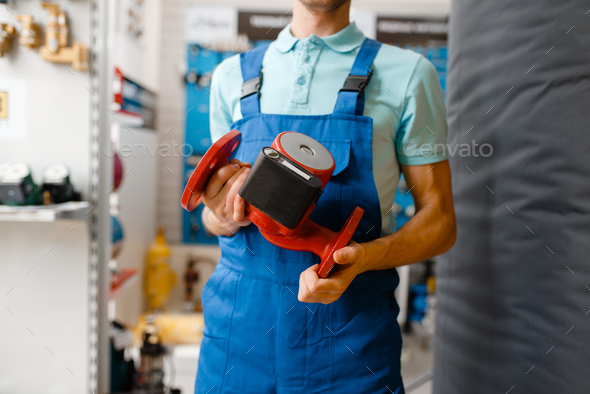 Plumber holds water pump, plumbering store - Stock Photo - Images