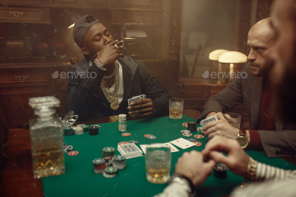 Poker players at gaming table with green cloth - Stock Photo - Images