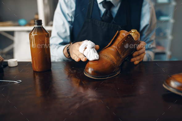 Shoemaker wipes black shoe polish, footwear repair - Stock Photo - Images
