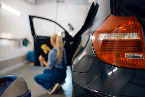 Female washer cleans automobile door trim - Stock Photo - Images