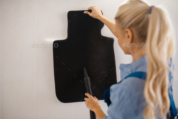 Female washer cleans automobile mats, car wash - Stock Photo - Images