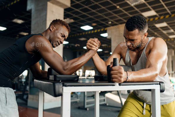 Two men fighting, arm wrestling training in gym - Stock Photo - Images