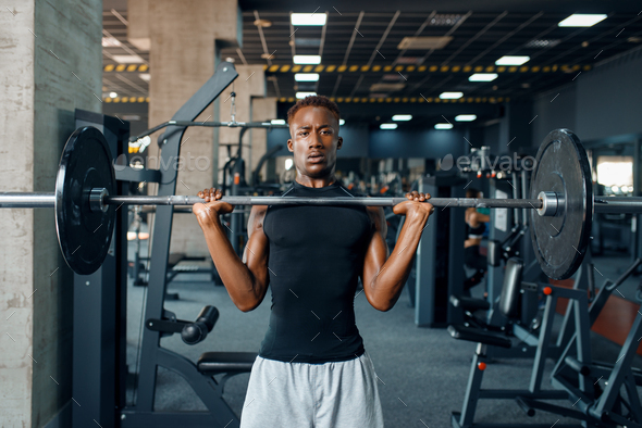 Athlete doing exercise with barbell in gym - Stock Photo - Images