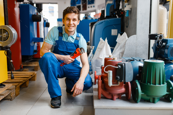 Plumber with pipe wrench at showcase in store - Stock Photo - Images