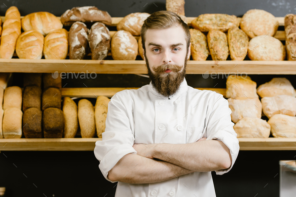 Charismatic baker stands on the background of shelves with fresh bread in the bakery - Stock Photo - Images