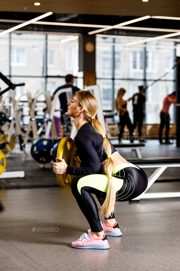 Slender girl with long blond hair dressed in sportswear is doing squats with plate in the modern gym - Stock Photo - Images