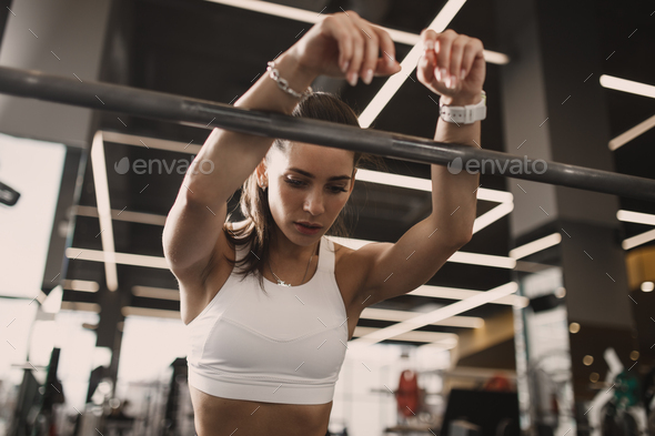 Athletic young brunet girl dressed in sportswear having rest next to the barbell in the modern gym - Stock Photo - Images