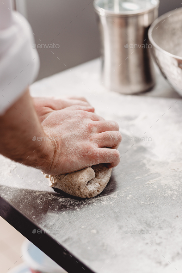 Baker punchs down the dough in the kitchen in the bakery - Stock Photo - Images