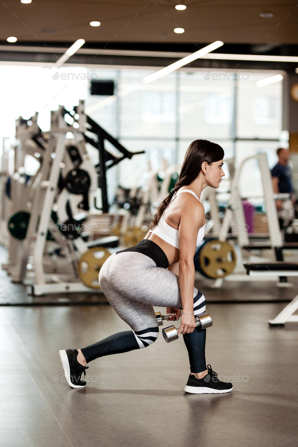 Slim brunette girl dressed in a sportswear is doing squats with dumbbells in the modern gym - Stock Photo - Images
