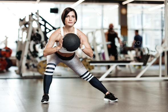 Slender brunette girl dressed in a sportswear is doing sports exercises with heavy fitness ball in - Stock Photo - Images