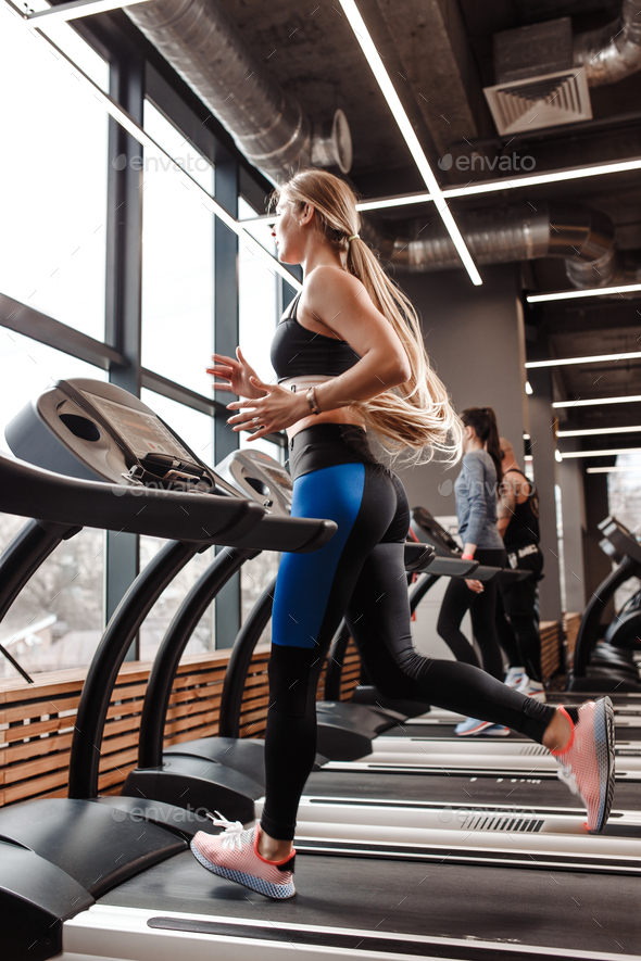 The athletic girl with long blond hair dressed in a sportswear is running on the treadmill in front - Stock Photo - Images