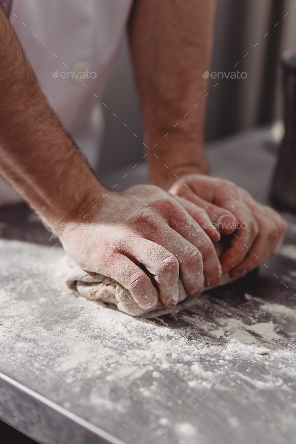 Professional baker kneads dough on the table in the kitchen of the bakery - Stock Photo - Images