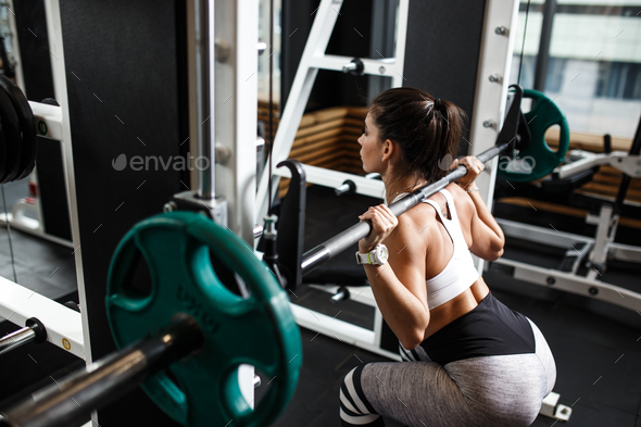 Young athletic girl dressed in sportswear squats with a barbell in the modern gym - Stock Photo - Images