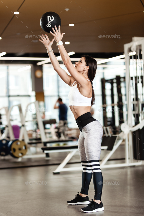 Athletic brunette girl dressed in a sportswear throws the fitness ball up in the modern gym - Stock Photo - Images