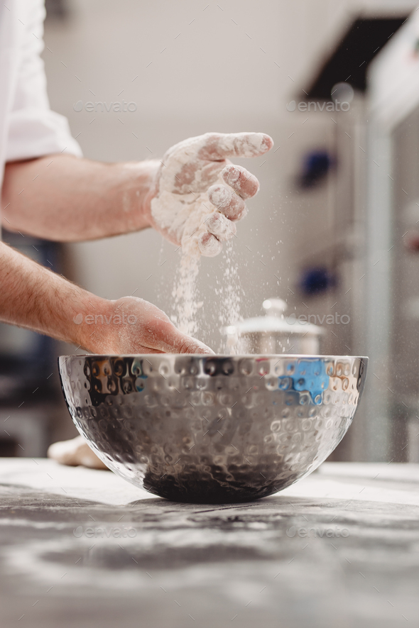 Baker adds flour to dough in an iron bowl on the table in the bakery - Stock Photo - Images